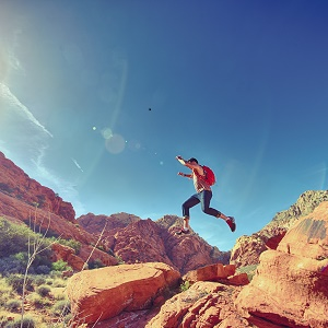 Athletic Man Jumping Between Rocks -